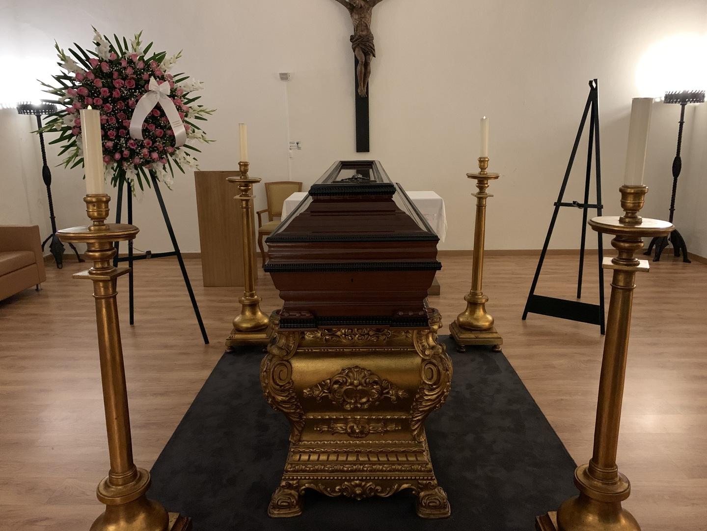 Sala mortuária com caixão em madeira sobre plataforma dourada com coroa de flores e velas