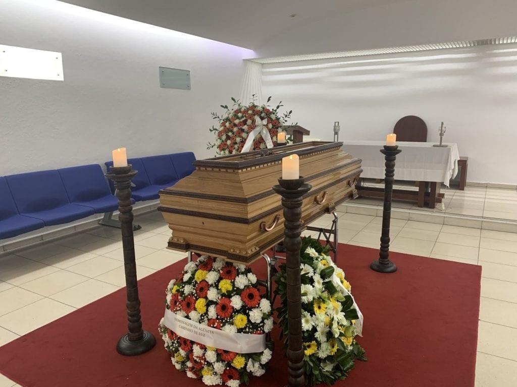 Sala mortuária com caixão em madeira, coroas de flores e candelabros com velas