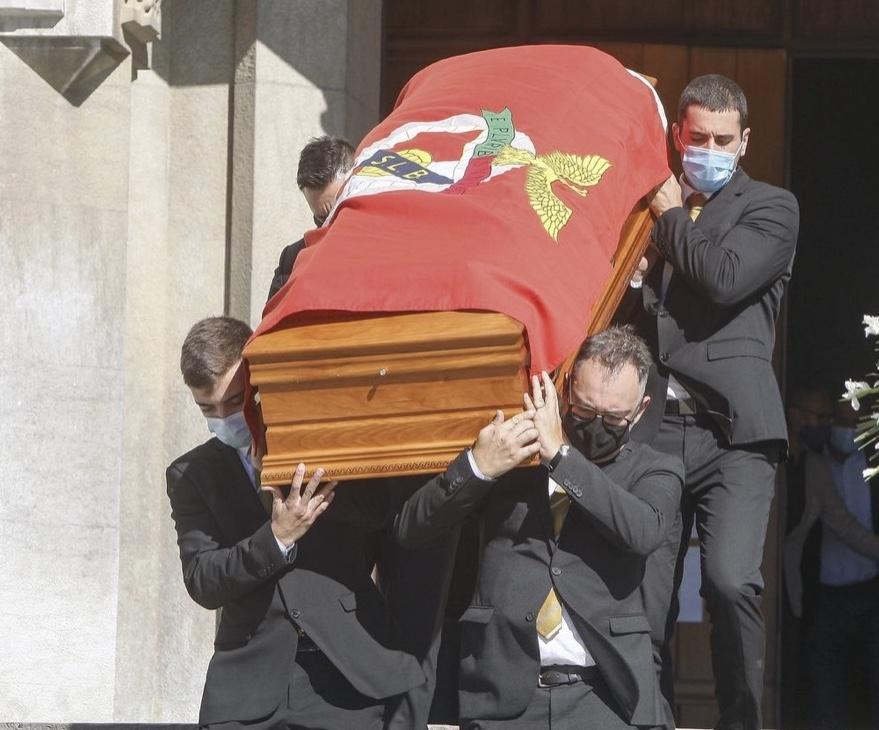 Quatro homens vestidos de preto e máscara carregam caixão de madeira coberto com bandeira SLB