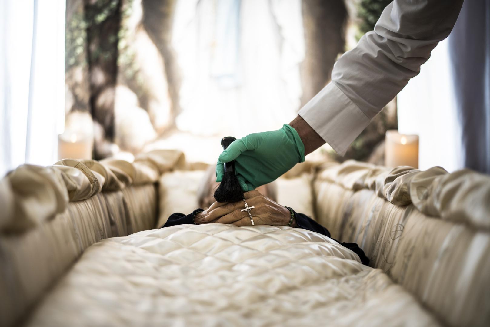 Braço de homem com luva cirúrgica segurando pincel, sobre caixão funerário com corpo de mulher