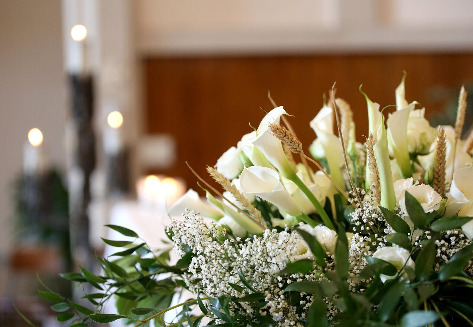 Pormenor de ramo de flores para funeral brancas com folhas verdes