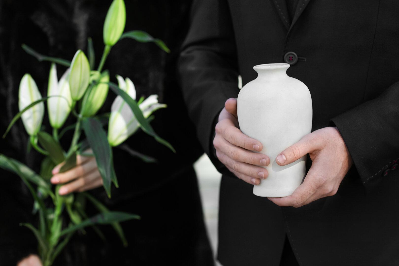 Homem vestido de preto com vaso branco nas mãos e outra pessoa com ramo de flores