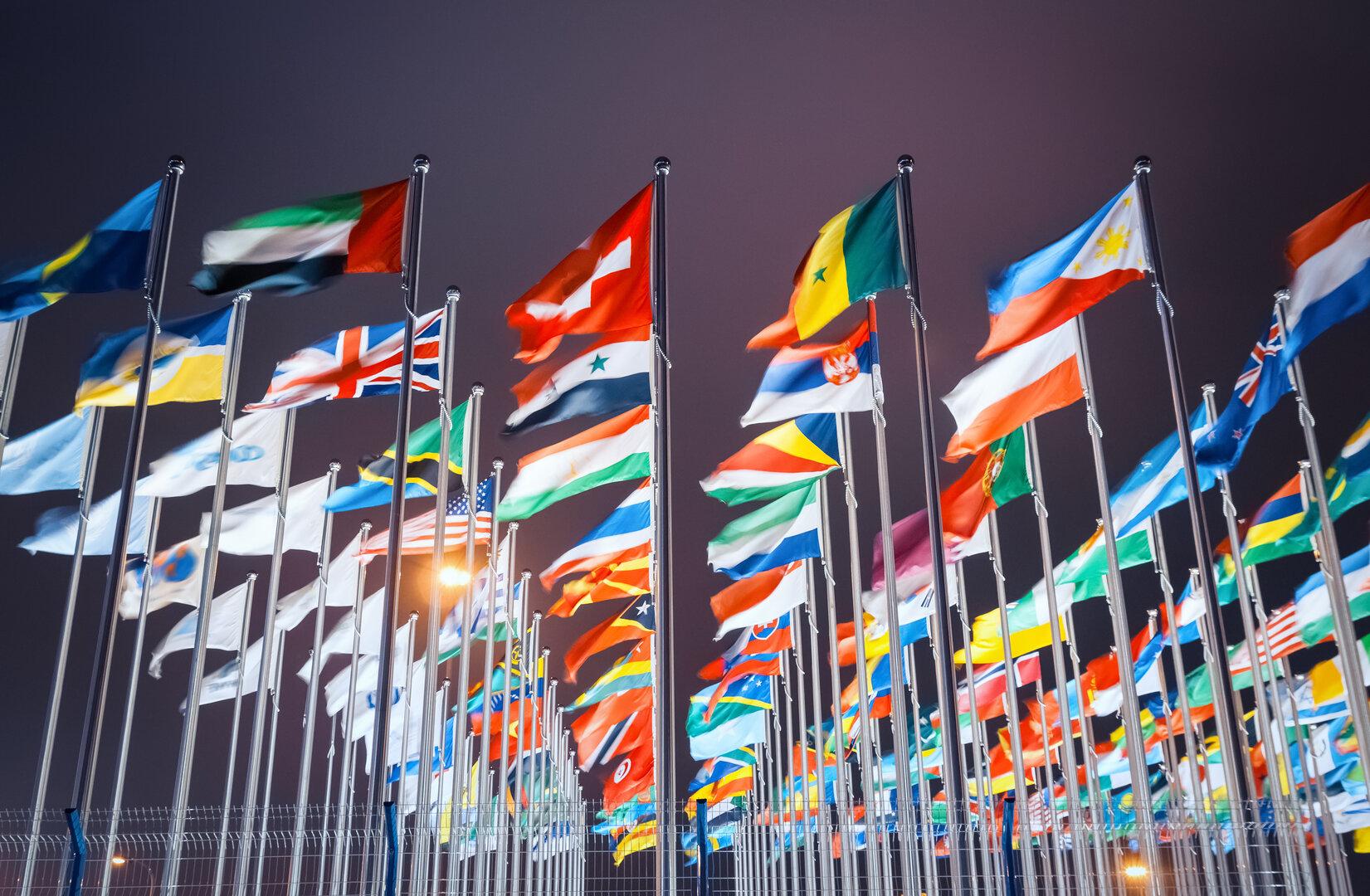 Conjunto de bandeiras de diversos países agitadas ao vento sobre fundo escuro